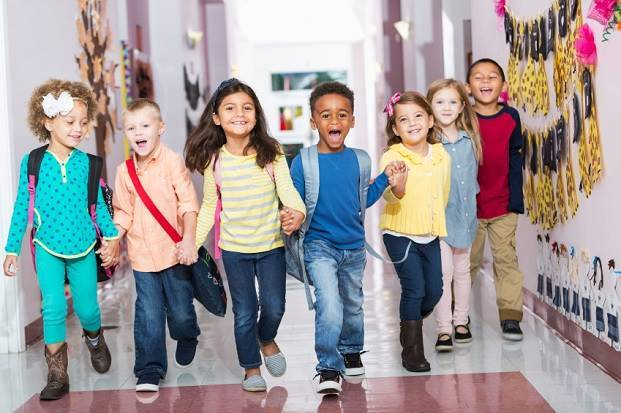 Multiracial group of preschoolers running down hallway demonstrating uni access for everyone